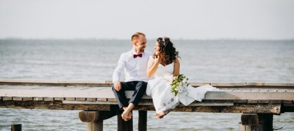 bride-and-groom-sitting-on-wooden-dock